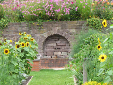 Photo of the garden showing flowerbeds with sunflowers and a green path leading to a stone walll