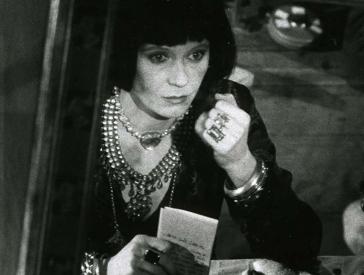 Filmszene in schwarz-weiß: Eine mit viel Schmuck behängte Frau schaut mit leerem Blick in einen Spiegel.