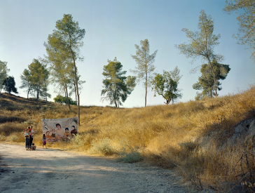 Photography: View into a landscape, at the left edge of the picture there is a family in front of a poster, on which people are depicted.