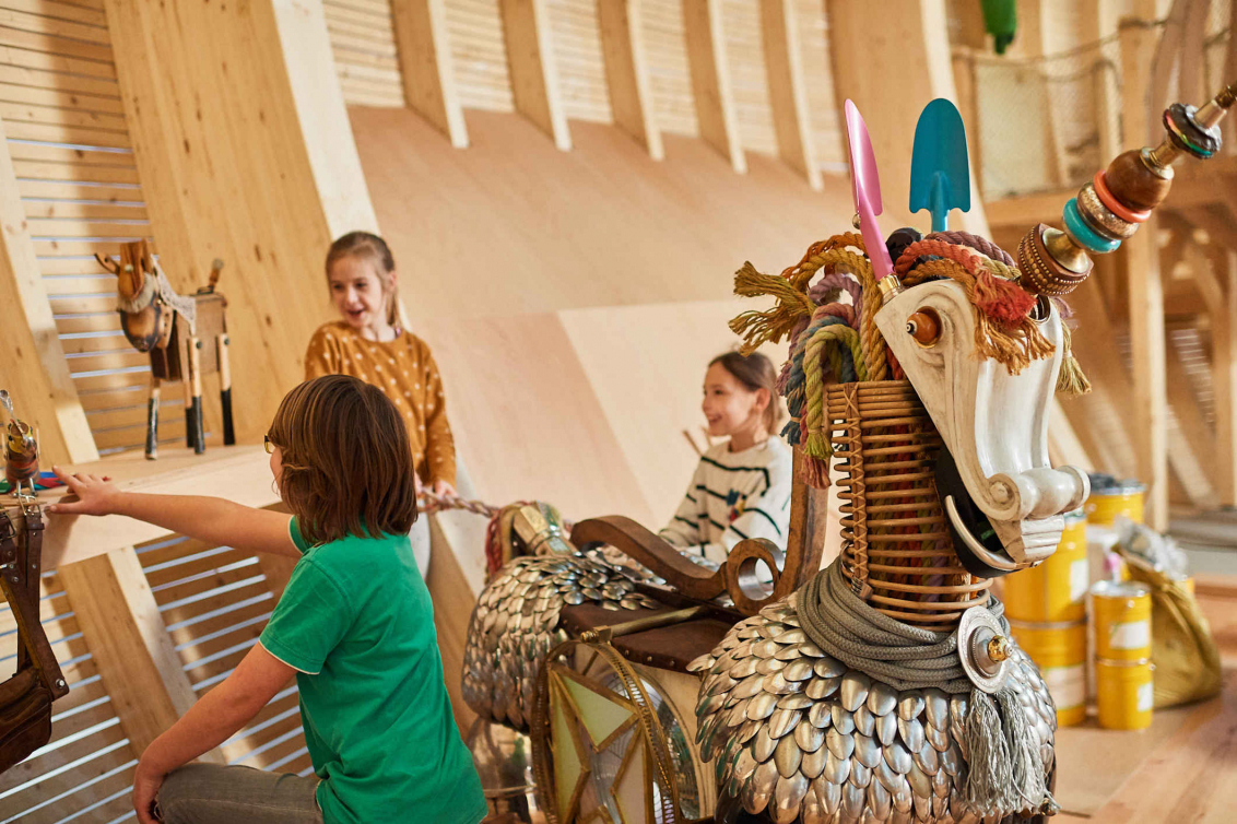 Ein aus Löffeln, Schaufeln und anderen Elementen gebautes Einhorn hinter dem Kinder stehen und spielen