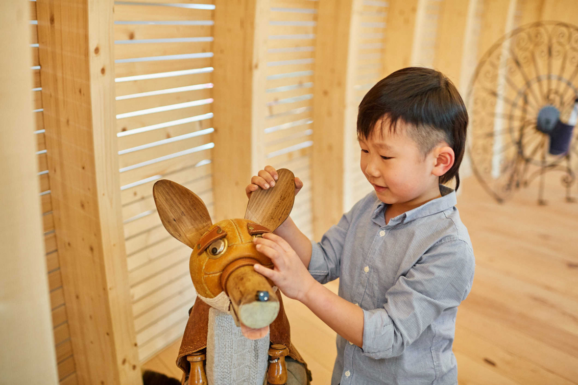 Child touches a fox built from a volleyball and wooden elements