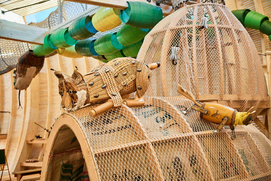 A lurking lynx made of everyday objects sits on a hut made of wood and net. In the background, a snake is meandering on the ceiling. It is composed of barrels