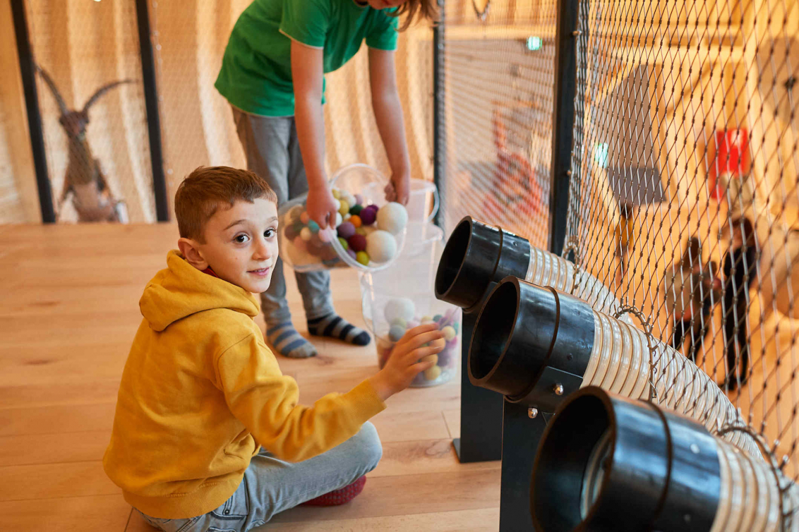 Child wearing a yellow sweatshirt is sitting in front of pipe openings into which he has thrown something. In the background another child filling balls from one transparent bucket into another
