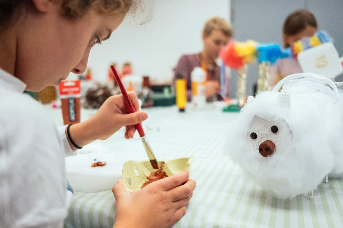 A child is painting on a pieace of cardboard, on a table there is a handcrafted sheep