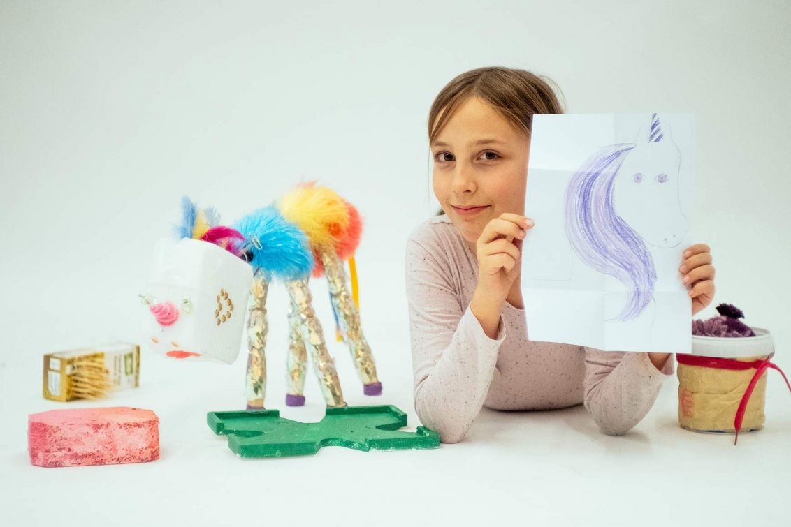 A child next to a handcrafted unicorn holds a drawing of a unicorn in the camera.