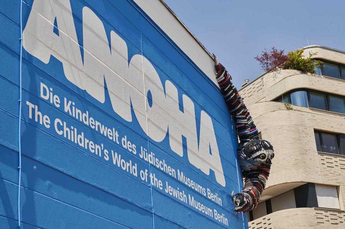 ANOHA-Schriftzug an einer Wand, an der ein Faultier aus Fahrradteilen hängt