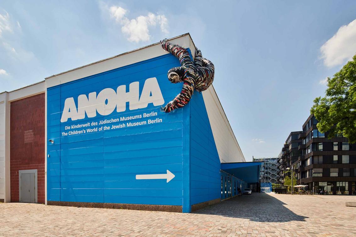 Blaues Gebäude mit Schriftzug, an dem ein Faultier aus Fahrradteilen hängt