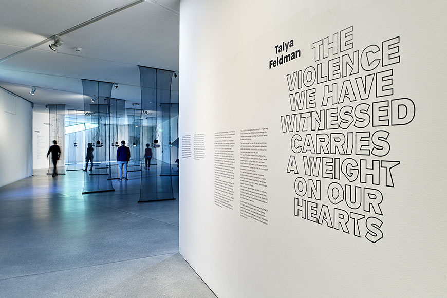 Room view of the exhibition with visitors, in the foreground a wall with text