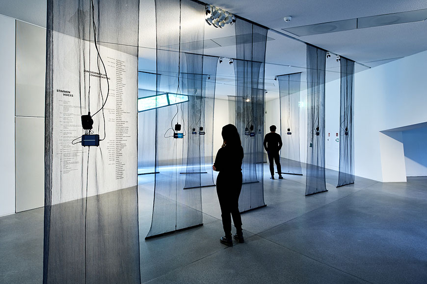 Room view of the exhibition with visitors, black transparent fabric panels hanging from the ceiling