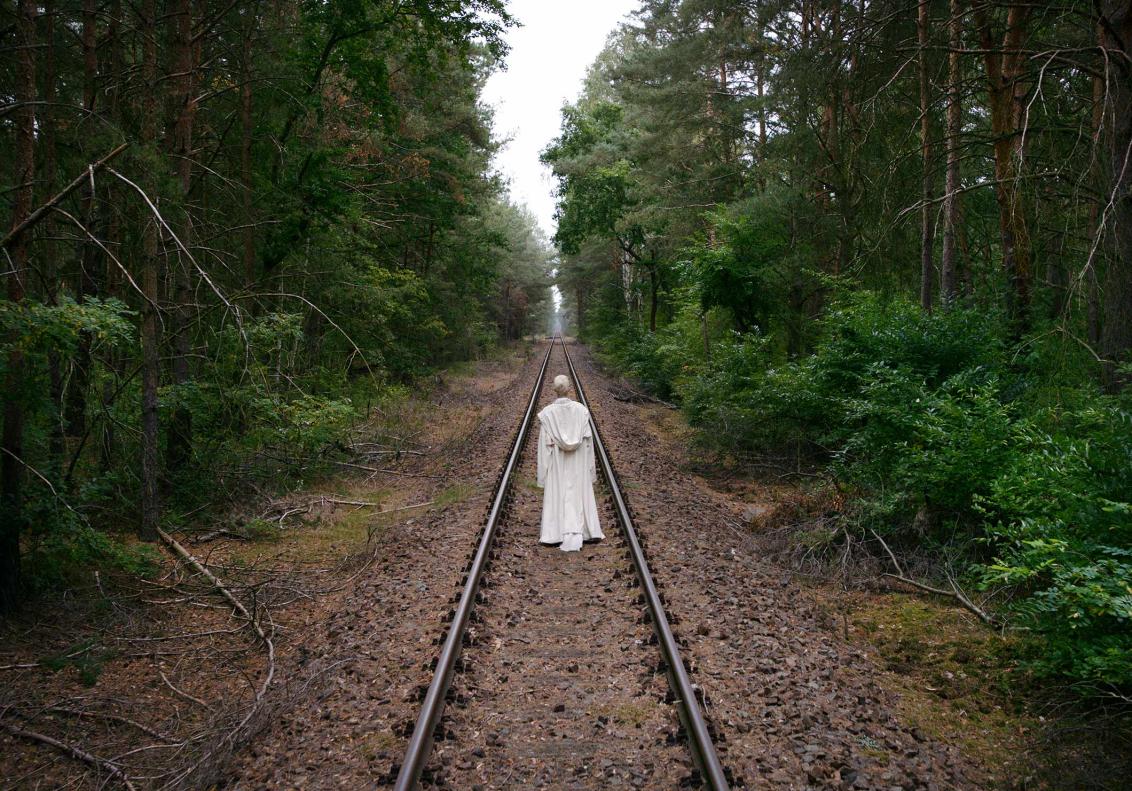 Film still with woman walking on railroad tracks
