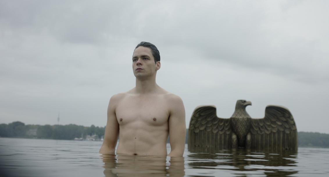 Filmstill mit Mann und Adlerfigur im Wasser
