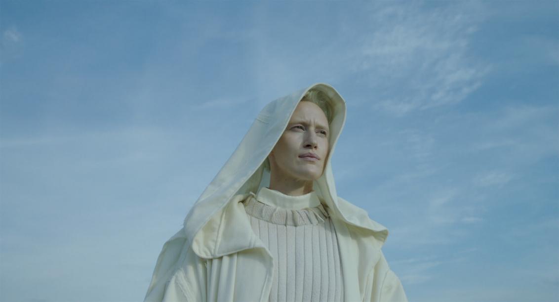 Oberkörper einer androyn wirkenden Person vor leuchtend blauem Himmel. Die Kappe ihres kuttenartigen Gewandes bedeckt ihr Haupt