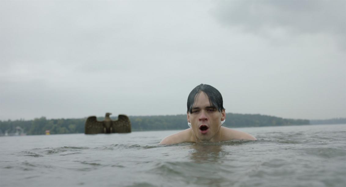 Vorne im Bild ist der nasse Kopf eines Schwimmers in einem See zu sehen. Schräg hinter ihm taucht aus dem Wasser gerade ein großer Reichsadler aus Metall auf. Der bewölkte Himmel und die Wasseroberfläche sind grau in grau und wirken bedrohlich