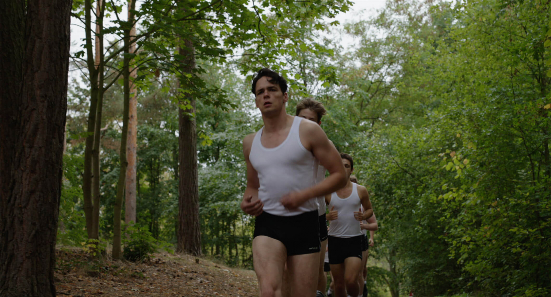 Eine Gruppe junger Männer in weißen Leibchen und schwarzen, sehr kurzen Hosen joggt im Gänsemarsch durch einen sommerlich-grünen Laubwald
