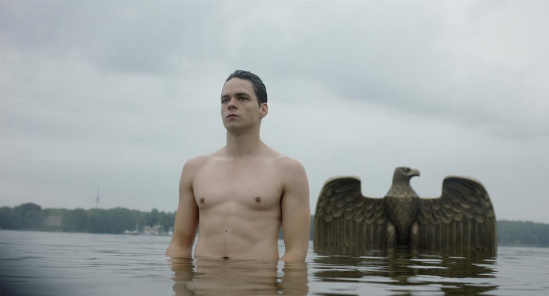 Ein Mann steht in einem See, zu sehen sind sein nackter Oberkörper und sein Kopf. Hinter ihm ragt ein metallener Reichsadler aus dem Wasser