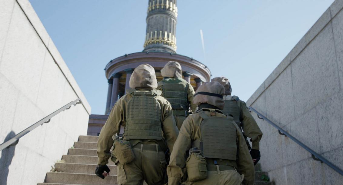 Vier Personen in olivgrünen Uniformen mit schusssicheren Westen, Helmen und Trinkflaschen auf der Treppe einer Unterführung. Man sieht die Männer von hinten, die Treppe führt nach oben zur Siegessäule