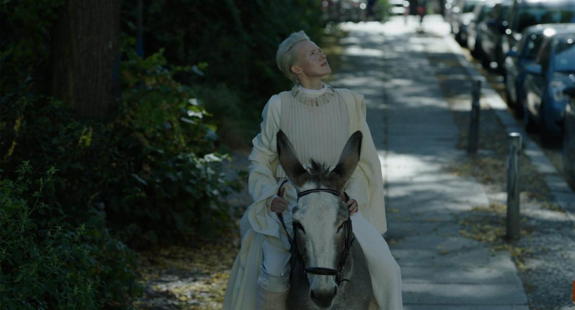 Eine weißgekleidete, platinblonde Frau reitet auf einem Esel im Halbschatten auf einem Fußgängerweg, links von ihr sind Bäume, rechts parkende Autos zu sehen. Sie legt den Kopf in den Nacken, ihr Blick geht nach rechts oben