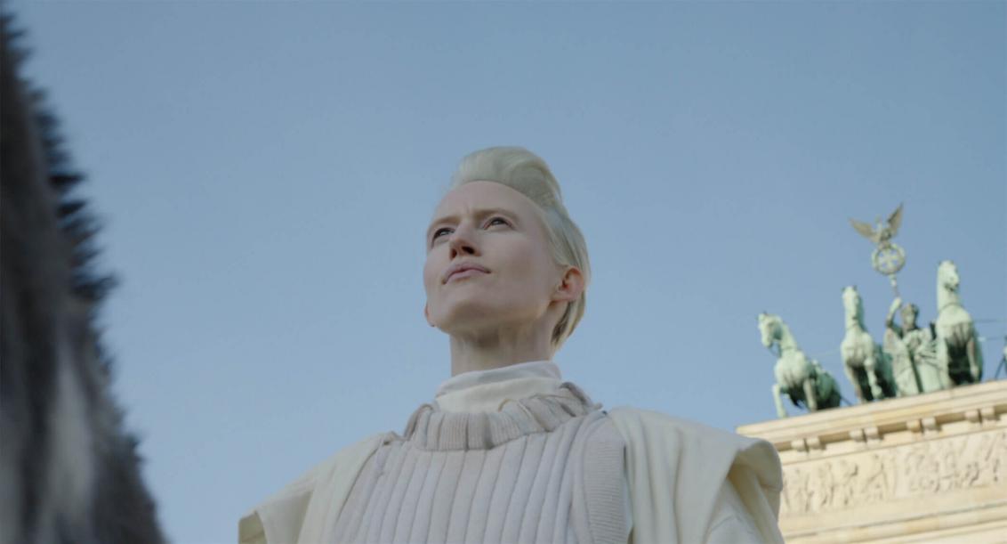 Brustbild einer platinblonden Frau mit kurzem Haar und weißem Oberteil vor leuchtend blauem Himmel. Sie ist von schräg unten fotografiert, rechts im Bild ist der obere Teil des Berliner Brandenburger Tors zu erkennen