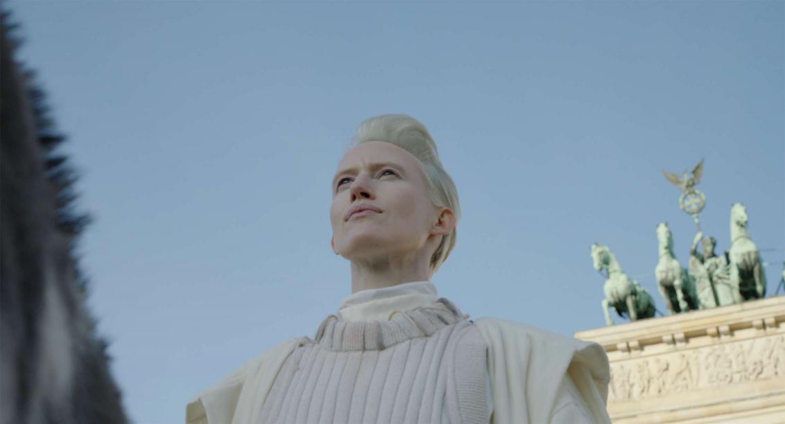 Blick aus Froschperspektive auf Brust und Gesicht einer weiß gekleidete Frau mit platinblondem, kurzem Haar auf einem Esel, dessen Hals am linken Bildrand angeschnitten knapp zu erkennen ist. Hintergrund: Berliner Brandenburger Tor und stahlblauer Himmel