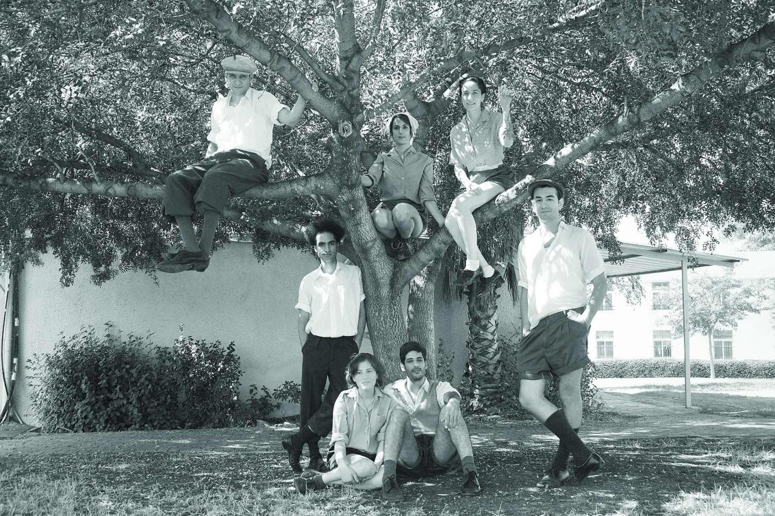 Schwarz-Weiß-Fotografie mit jungen Menschen in sommerlicher Kleidung. Zwei sitzen vor einem Baum im Gras, zwei stehen unter dem Baum, drei sitzen darin. Alle schauen in die Kamera, im Hintergrund ist ein Haus zu sehen.