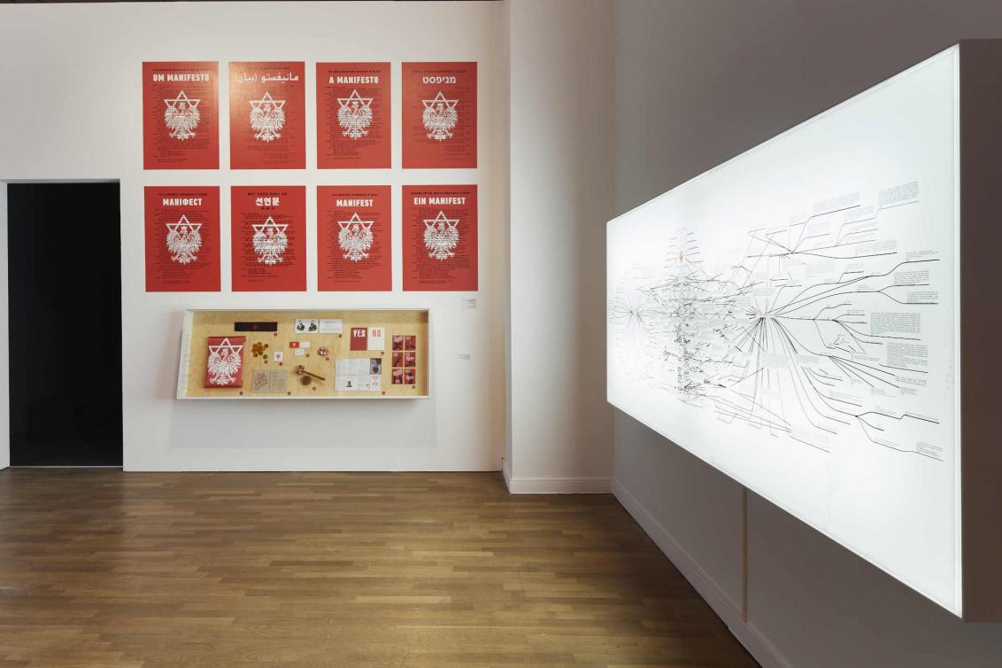 Raumansicht mit großer Medien-Installation und roten Plakaten