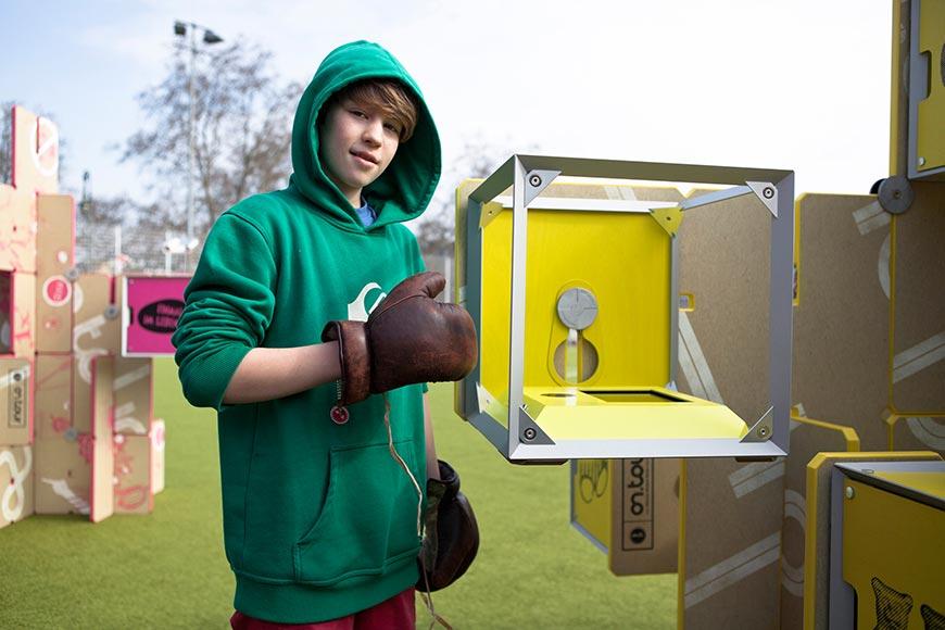 Ein Schüler mit Boxhandschuhen an einer Ausstellungsvitrine