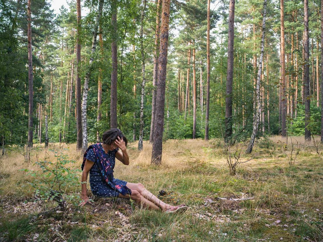 Fotografie einer Frau im blauen Sommerkleid, die im Wald auf dem Boden sitzt und sich über der Stirn in die Haare greift