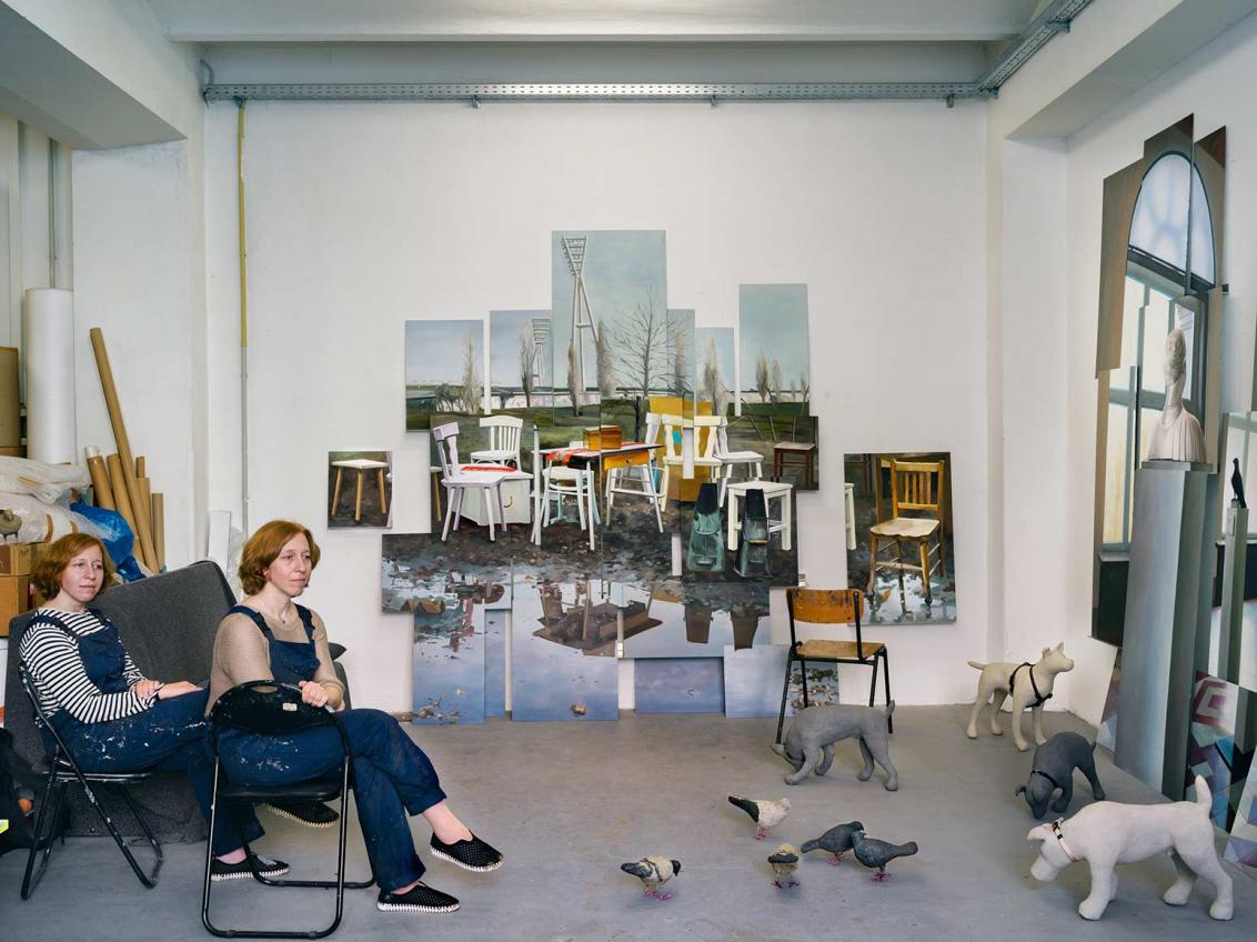 Fotografie zweier Zwillingsschwestern in blauen Latzhosen auf Klappstühlen in einem Atelier, an der Wand ein Bild mit Stuhl-Motiven, auf dem Boden Hunde- und Taubenskulpturen