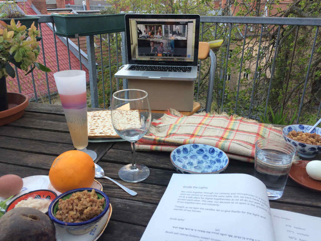 On a wooden table there are various glasses, plates with dishes, bowls and an open book. On a plate lies an orange. Behind the table there is a laptop on a cardboard box, in which a video call can be seen.