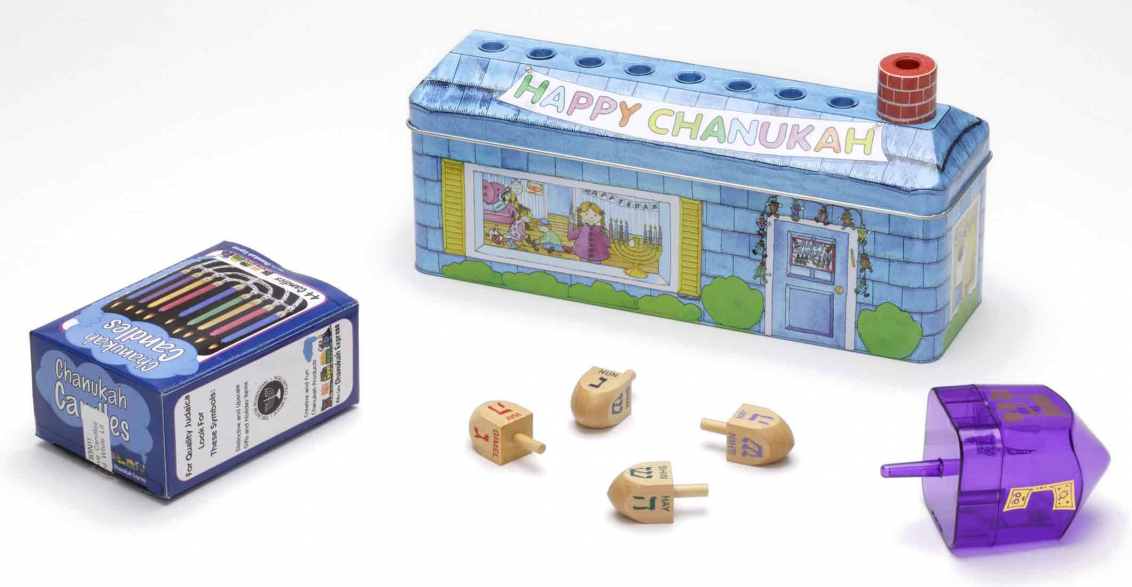 Multi-piece children's set for Hanukkah consisting of dreidels, candles, and a menorah in the form of a metal box decorated to resemble a house. The roof features eight depressions to hold the candles; the chimney serves as the shamash.