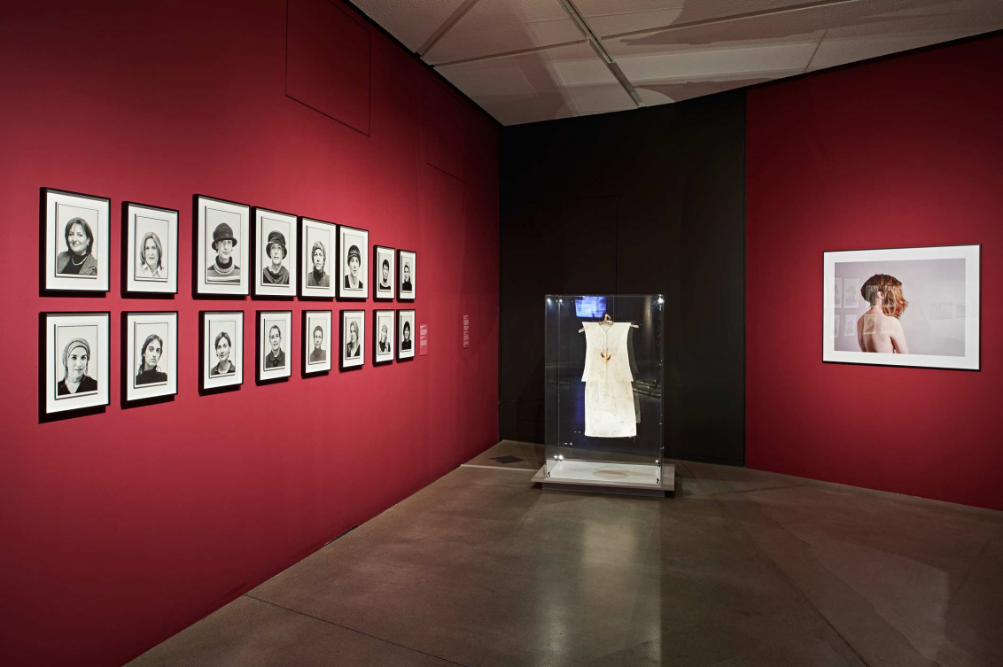 View of a room in the exhibition Cherchez la femme with portraits of women on one wall, a dress in a glass case, and a photo of a woman with two wigs on another wall