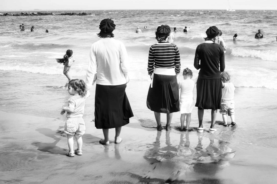 Schwarz-Weiss-Foto von Kleinkindern und orthodoxen Jüdinnen mit Kopfbedeckung und Rock am Strand, von hinten fotografiert