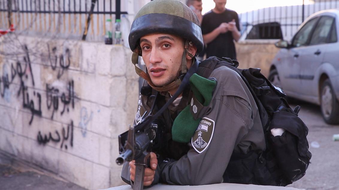 Soldat in Tarnuniform mit Helm und Waffe im Anschlag schaut in die Kamera und zielt Richtung Betrachter*in