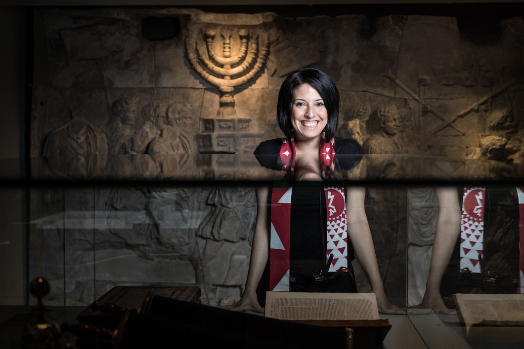 A laughing woman standing in a room of the exhibition Welcome to Jerusalem