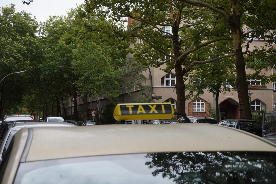 Color photo: Taxi on a tree-lined street