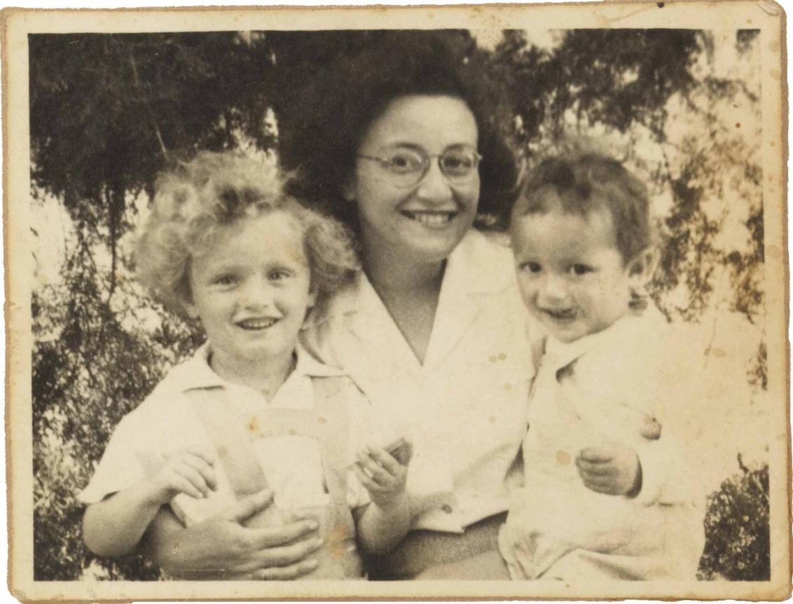 Schwarz-Weiß-Fotografie: Leonie sitzt in der Mitte und lächtelt breit. Auf ihrem Schoß sitzt Michael, der sich mit der Zunge über den rechten Mundwinkel fährt. Links steht Peter-Uri mit hellen Locken, ebenfalls breit lächelnd.
