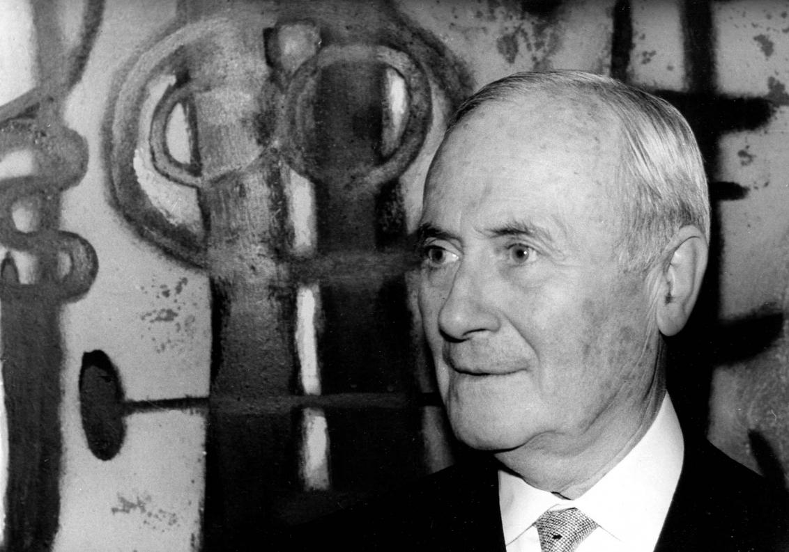 Schwarz-Weiss-Porträt von Joan Miró im Halbprofil vor einem Gemälde
