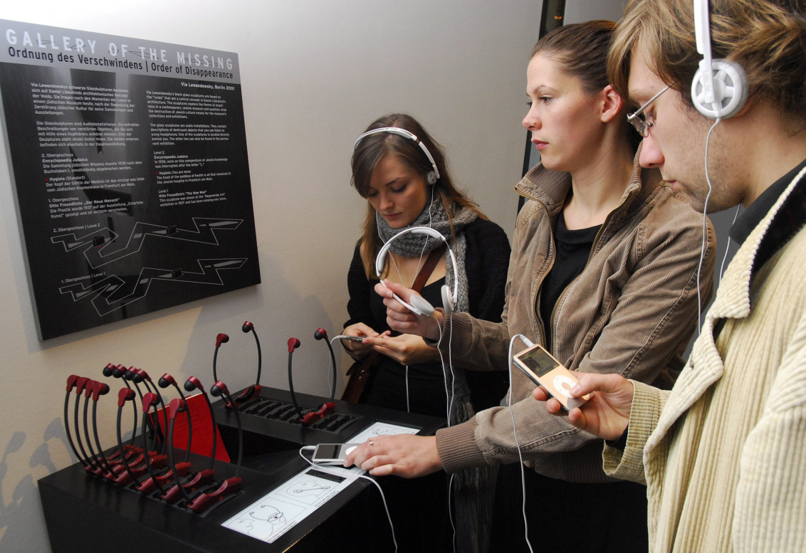 Three visitors with headphones and output station with headphones
