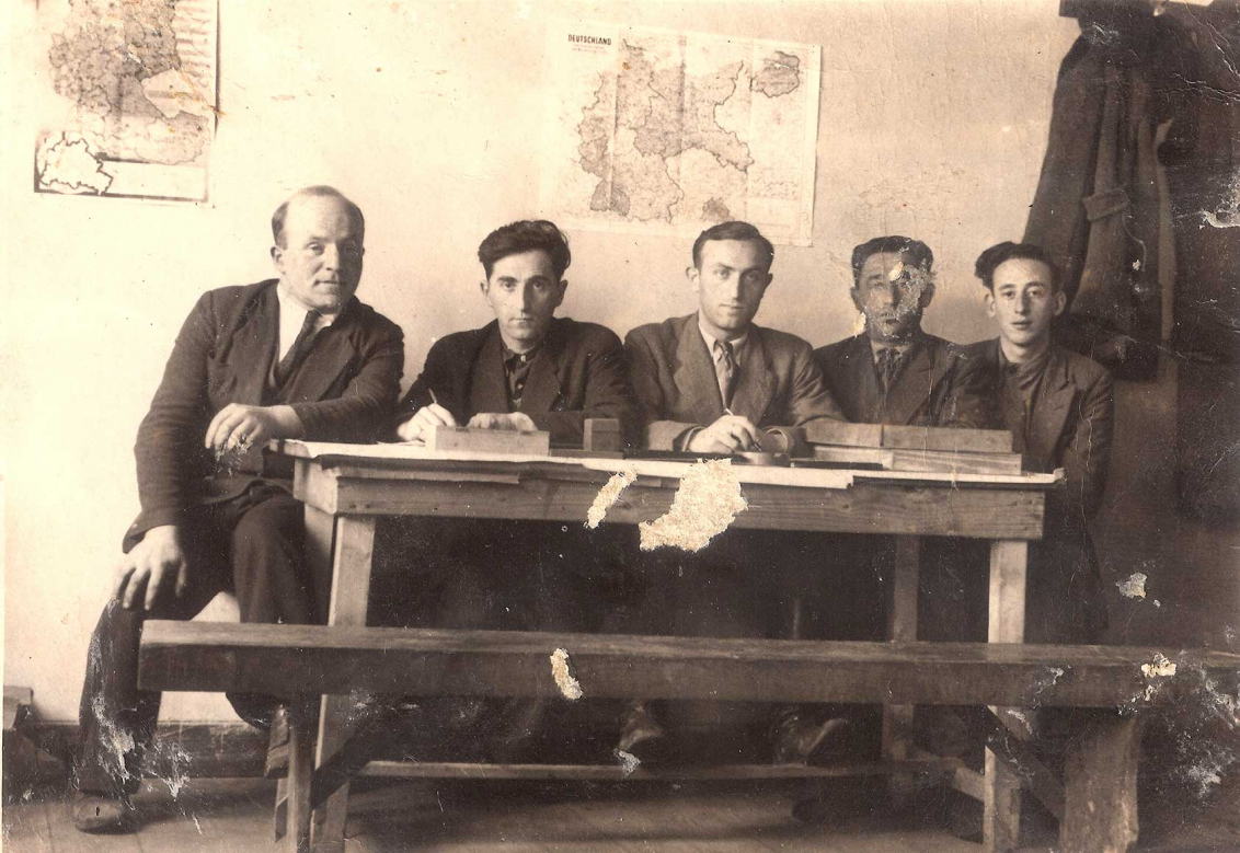 Black and white photograph of five men sitting side by side at a wooden table with two maps hanging on the wall behind them