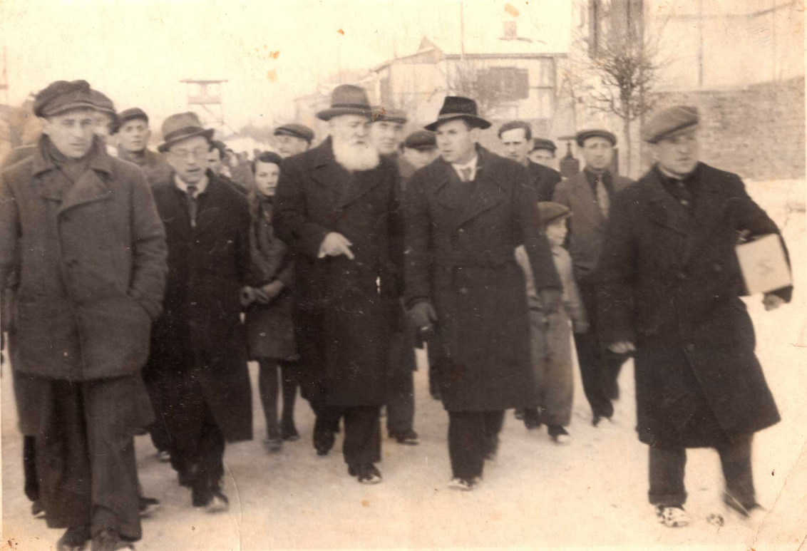 Black and white photo of a larger group of people in coats and hats walking towards the viewer