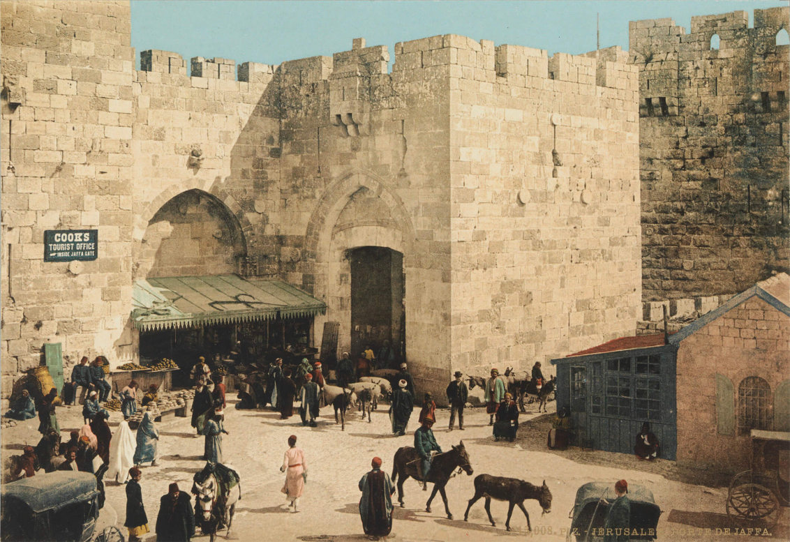 Colored photograph showing people, market stalls, donkeys and a car