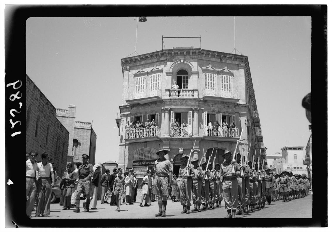 Das Foto in Schwarz-Weiß zeigt eine prunkvolle Fassade mit Balkonen. Darauf stehen Menschen, die auf den Aufmarsch bewaffneter Soldaten in Uniform schauen, der vor dem Gebäude stattfindet.