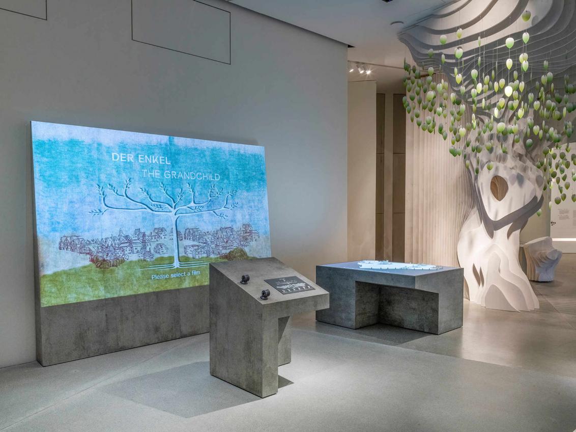 Ausstellungsraum mit Beton-Ausstellungsmöbeln, einer Projektion von einem Baum, um den eine grüne Wiese und Häuser stehen