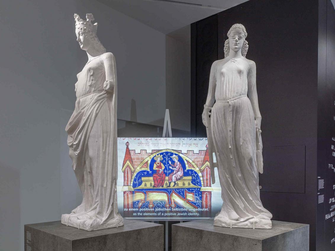 Zwei weiße Skulpturen, im Hintergrund eine Leinwand, auf der ein Film läuft