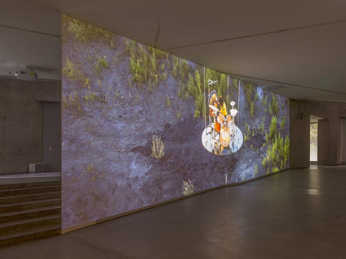 Raumansicht Rafael Roth Galerie, auf einer großen Leinwand ist ein Schlagzeuger zu sehen, der auf einer Fläche mit schwarzem Sand und Gras spielt