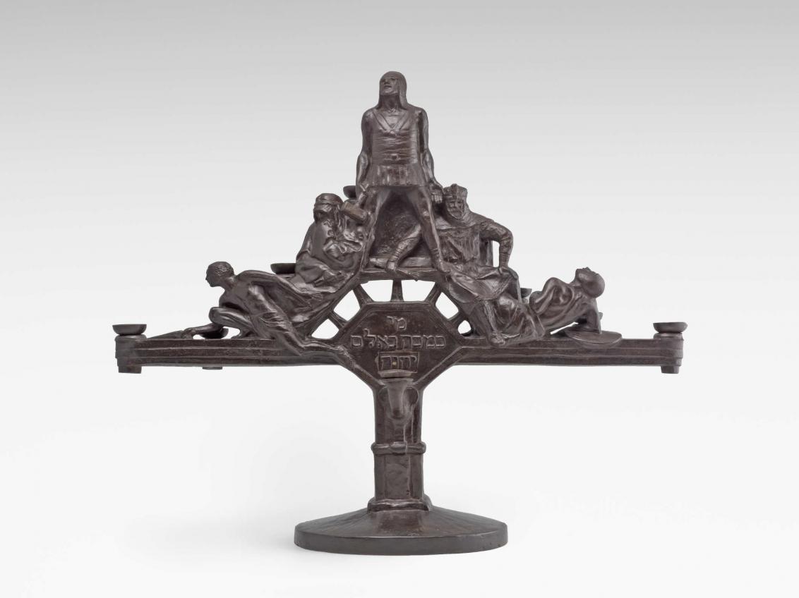 Metallener Kerzenständern mit Figuren und hebräischer Schrift