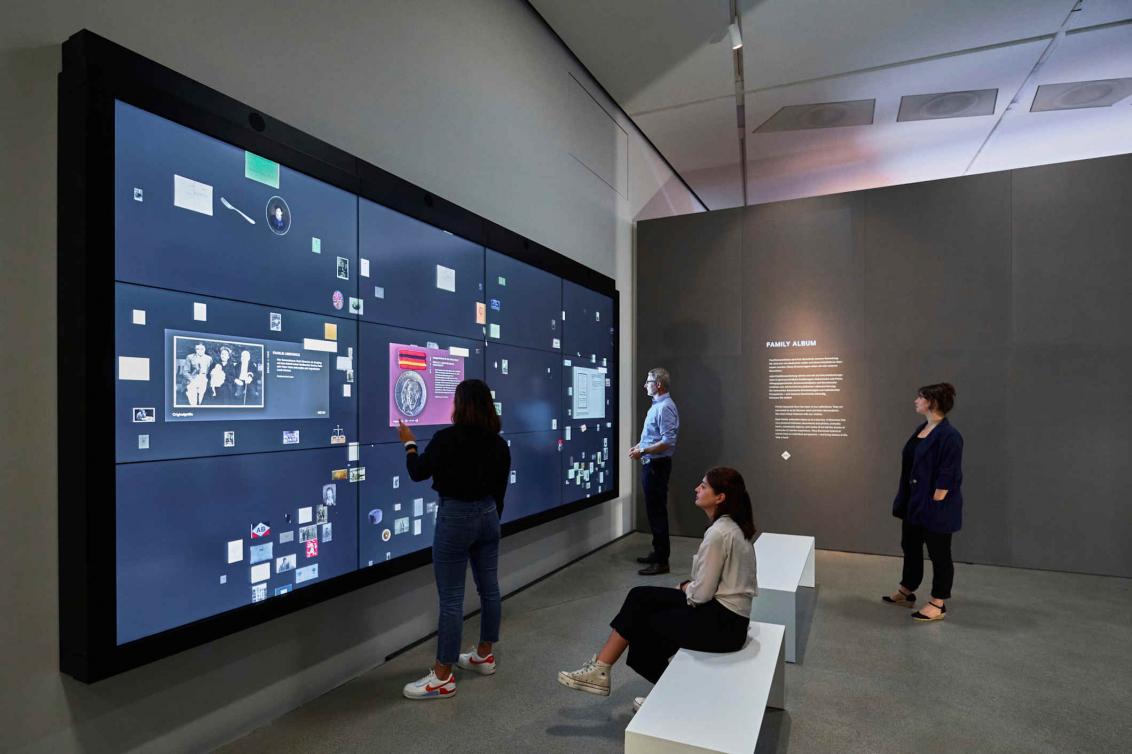 Medienstation mit einem großen Bildschirm vor der mehreren Personen stehen