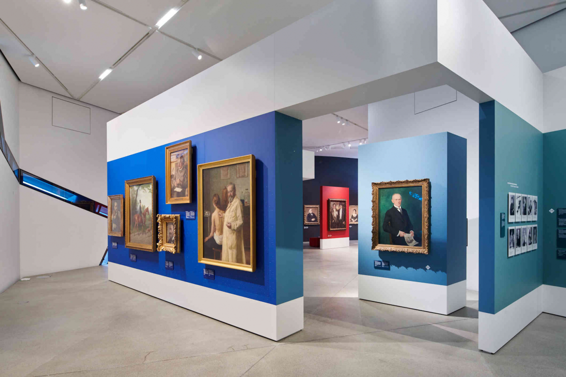 View of paintings hanging on blue and turquoise walls