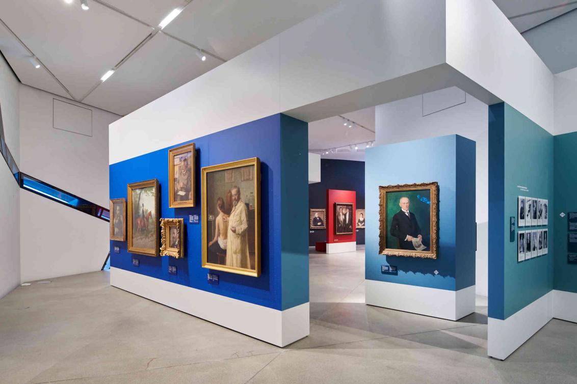 Blick auf Gemälde, die an blauen und türkisenen Wänden hängen