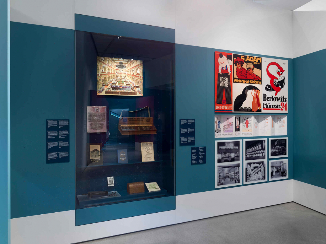 Showcase with exhibition objects and posters on a blue wall